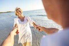 Pares superiores felizes que andam guardarando a praia tropical das mãos Imagens de Stock