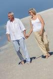 Pares superiores felizes que andam guardarando a praia tropical das mãos Imagem de Stock Royalty Free