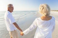 Pares superiores felizes que andam guardarando a praia tropical das mãos Imagem de Stock