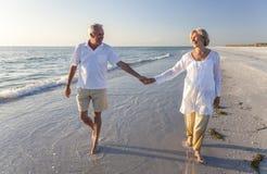 Pares superiores felizes que andam guardarando a praia tropical das mãos Foto de Stock