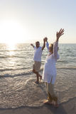 Pares superiores felizes que andam guardarando a praia tropical das mãos Fotografia de Stock Royalty Free