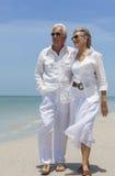 Pares superiores felizes que andam pelo mar na praia tropical Fotografia de Stock Royalty Free