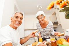 Pares superiores felizes que comem o café da manhã imagens de stock