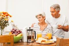 Pares superiores felizes que comem o café da manhã imagens de stock royalty free