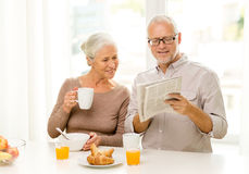 Pares superiores felizes que comem o café da manhã em casa imagens de stock royalty free