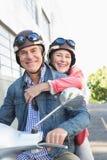 Pares superiores felizes que montam uma bicicleta motorizada imagens de stock royalty free