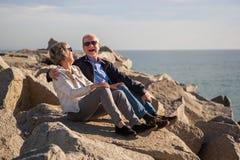 Pares superiores felizes que sentam-se em rochas pelo mar imagens de stock