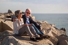 Pares superiores felizes que sentam-se em rochas pelo mar foto de stock