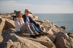 Pares superiores felizes que sentam-se em rochas pelo mar fotografia de stock royalty free