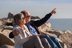 Pares superiores felizes que sentam-se em rochas pelo mar foto de stock royalty free