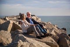 Pares superiores felizes que sentam-se em rochas pelo mar fotos de stock