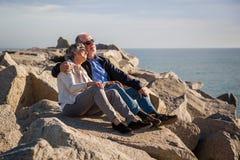 Pares superiores felizes que sentam-se em rochas pelo mar imagem de stock