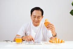 Pares superiores felizes que têm o café da manhã do croissant em casa e a bebida foto de stock