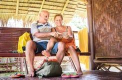 Pares superiores felizes usando o telefone esperto móvel no recurso de luxo do bungalow - pessoas idosas ativas e conceito do cur fotos de stock royalty free