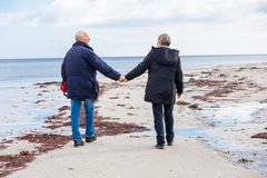Pares superiores idosos felizes que andam na praia fotos de stock
