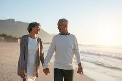 Pares superiores loving que dão uma volta junto na praia imagem de stock