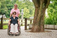 Pares superiores na cadeira de rodas, apreciando um dia no parque foto de stock
