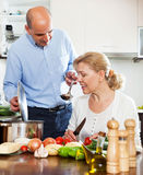 Pares superiores na cozinha que prepara o almoço fotografia de stock