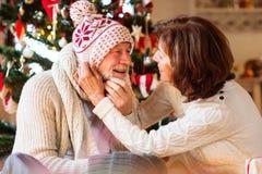 Pares superiores na frente da árvore de Natal que aprecia presentes Fotos de Stock Royalty Free