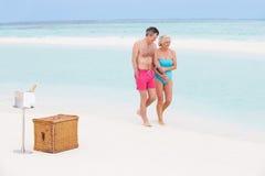Pares superiores na praia com Champagne Picnic luxuoso foto de stock