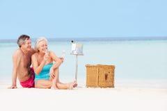 Pares superiores na praia com Champagne Picnic luxuoso foto de stock royalty free
