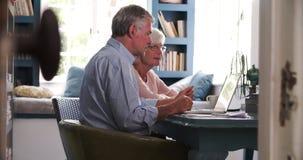 Pares superiores preocupados no escritório domiciliário que olha o portátil