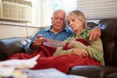 Pares superiores preocupados que sentam-se em Sofa Looking At Bills Imagens de Stock