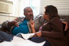 Pares superiores preocupados que sentam-se em Sofa Looking At Bills Imagens de Stock Royalty Free