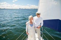 Pares superiores que abraçam no barco ou no iate de vela no mar Fotografia de Stock