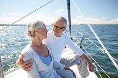 Pares superiores que abraçam no barco ou no iate de vela no mar Fotografia de Stock Royalty Free