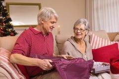 Pares superiores que abrem um presente de Natal no sofá Imagem de Stock Royalty Free