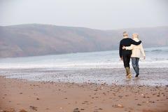 Pares superiores que andam ao longo da praia do inverno imagem de stock royalty free