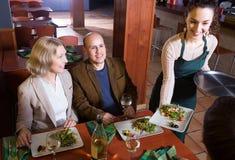 Pares superiores que apreciam o alimento no restaurante foto de stock royalty free