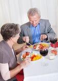 Pares superiores que apreciam o jantar junto Fotos de Stock Royalty Free