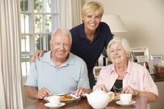 Pares superiores que apreciam a refeição junto em casa com ajuda home Imagens de Stock Royalty Free