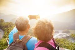 Pares superiores que caminham em montanhas e que tomam selfies Fotografia de Stock