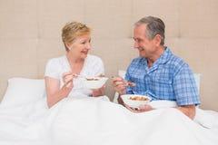 Pares superiores que comem o café da manhã na cama Imagens de Stock