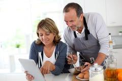 Pares superiores que cozinham com a tabuleta na cozinha imagens de stock