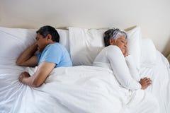 Pares superiores que dormem junto na cama no quarto fotos de stock