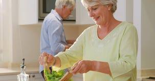 Pares superiores que falam ao misturar uma salada na cozinha video estoque