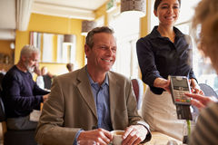 Pares superiores que fazem o pagamento do cartão à empregada de mesa no restaurante imagens de stock royalty free