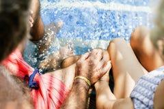 Pares superiores que guardam as mãos pela piscina fotografia de stock