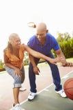 Pares superiores que jogam o basquetebol junto Imagens de Stock