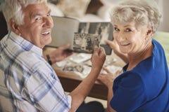 Pares superiores que olham suas fotos velhas foto de stock