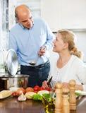 Pares superiores que preparam um almoço saudável em sua cozinha foto de stock
