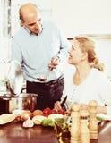 Pares superiores que preparam um almoço saudável em sua cozinha fotografia de stock royalty free