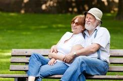 Pares superiores que sentam-se em um banco de parque Fotografia de Stock Royalty Free