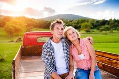 Pares superiores que sentam-se na parte de trás do camionete vermelho Fotos de Stock Royalty Free