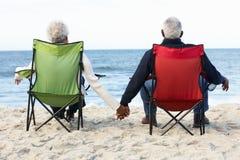 Pares superiores que sentam-se na praia em Deckchairs Fotografia de Stock Royalty Free