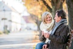 Pares superiores que sentam-se no banco, café bebendo Natureza do outono Imagem de Stock